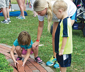 Kids placing ALS Memory Bricks